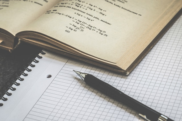 Graph paper with pen and math book
